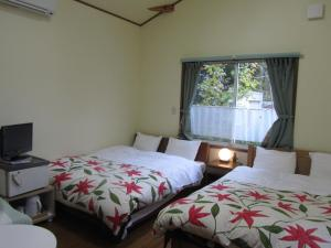 A bed or beds in a room at Cottage Pension Marimo