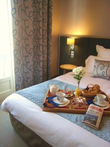 A bed or beds in a room at Hôtel Le Goyen