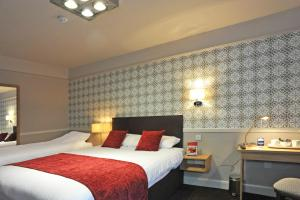 A bed or beds in a room at The Kings Head Wroxham by Greene King Inns