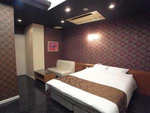 A bed or beds in a room at Hotel Carneval (Adult Only)