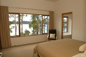 A bed or beds in a room at Stewarts Bay Lodge