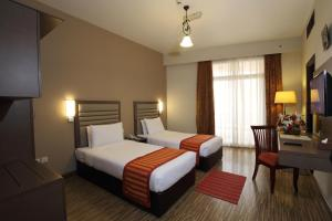 A bed or beds in a room at Wave International Hotel