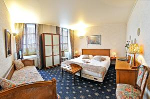 A bed or beds in a room at Le Grand Monarque
