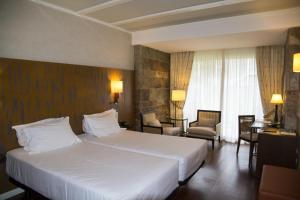 A bed or beds in a room at Hotel Nuevo Portil Golf