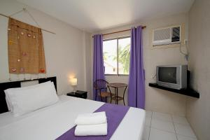 A bed or beds in a room at MR Holidays Hotel