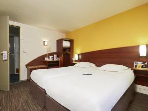 Un ou plusieurs lits dans un hébergement de l'établissement Comfort Hotel Etampes