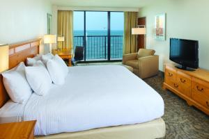 A bed or beds in a room at DoubleTree by Hilton Atlantic Beach Oceanfront