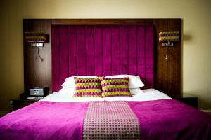 A bed or beds in a room at The Parklands Hotel