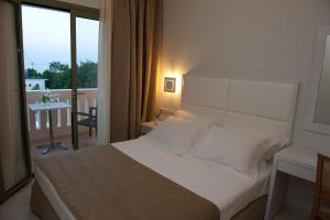 A bed or beds in a room at Aphrodite Hotel & Suites
