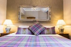 A bed or beds in a room at Muckrach Country House Hotel