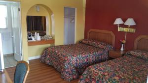 A bed or beds in a room at Slumber Motel