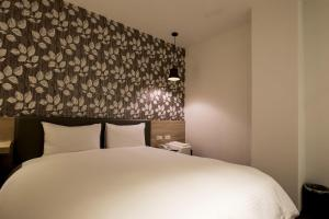 A bed or beds in a room at Queens Hotel II