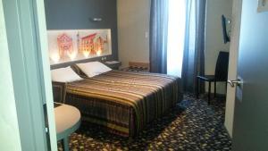 A bed or beds in a room at Hôtel de La Cloche
