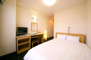 A bed or beds in a room at Heiwadai Hotel Tenjin