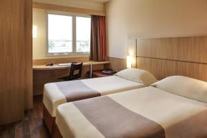A bed or beds in a room at Ibis Sofia Airport Hotel