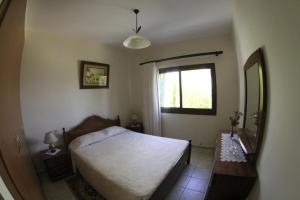A bed or beds in a room at Eve Pissouri Rozaki Villa