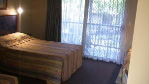 A bed or beds in a room at Bushland Beach Tavern