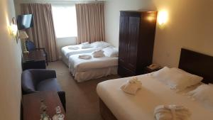 A bed or beds in a room at Skylark Hotel