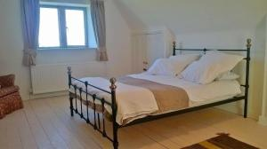 A bed or beds in a room at Battens Farm Cottages B&B