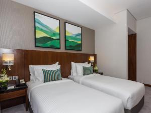 A bed or beds in a room at Flora Al Barsha Hotel At The Mall