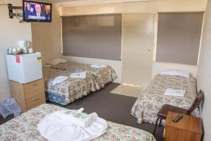 A bed or beds in a room at The Swiss Motel