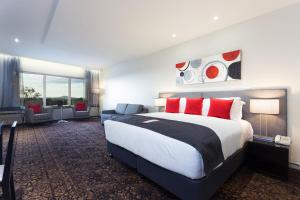 A bed or beds in a room at Calamvale Hotel Suites and Conference Centre