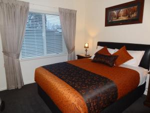 A bed or beds in a room at Hahndorf Oak Tree Cottages
