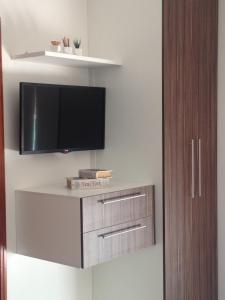 A television and/or entertainment center at Auxerre Flats e Hotel