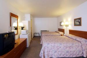A bed or beds in a room at Town House Motel