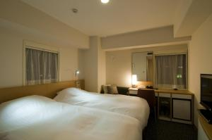 A bed or beds in a room at Hotel Sunflex Kagoshima