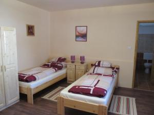 A bed or beds in a room at Tavi Fészek Vendégház