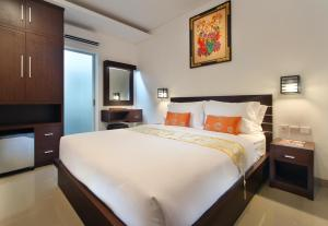 A bed or beds in a room at Lotus Tirta Seminyak