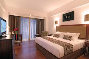 A bed or beds in a room at Kuta Paradiso Hotel