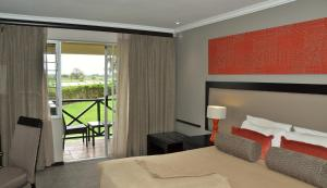 A bed or beds in a room at Cresta Riley's Hotel