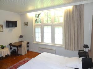 A bed or beds in a room at Hotel Kasteelhof 'T Hooghe