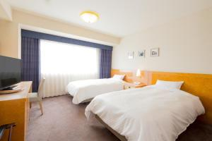 A bed or beds in a room at Beppu Kamenoi Hotel