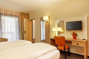 Ein Bett oder Betten in einem Zimmer der Unterkunft H4 Hotel Arcadia Locarno