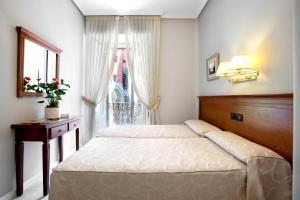 A bed or beds in a room at Hostal Macarena