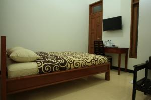 A bed or beds in a room at Puri Kusuma Guest House