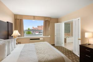 A bed or beds in a room at Days Inn & Suites by Wyndham North Bay