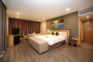 A bed or beds in a room at Dragon Sea Hotel