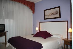 A bed or beds in a room at Hotel Cuatro Calzadas