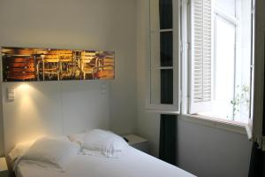 A bed or beds in a room at Raval Rooms