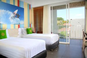 A bed or beds in a room at Bliss Surfer Hotel