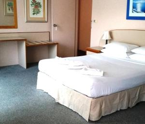 A bed or beds in a room at Forstay Motel