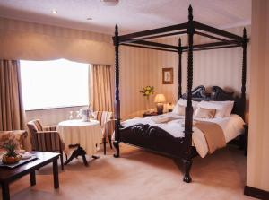 A bed or beds in a room at Seven Oaks Hotel