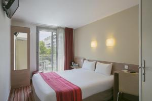 A bed or beds in a room at Kyriad Hotel Paris Bercy Village