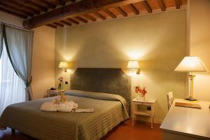 A bed or beds in a room at Borgo Sant'ippolito Country Hotel