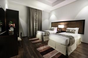 سرير أو أسرّة في غرفة في دوست للأجنحة الفندقية
