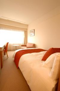 A bed or beds in a room at Nakano Sunplaza Hotel